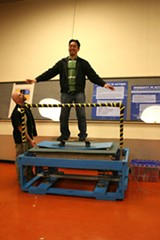 Peter Chea balances on a skateboard atop an earthquake simulator.