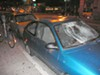 Two cars with smashed windows on 14th Street, where protesters left a trail of vandalism.