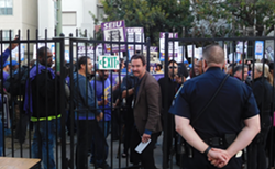 East Bay Times reporter David DeBolt is booed as he walks past the picket line to report on the mayor's speech.