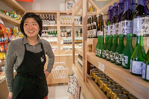 Yoko Kumano surrounded by sake at Umami Mart. - BERT JOHNSON/FILE PHOTO