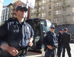 SFPD officers guard a bus carrying Oakland Mayor Libby Schaaf. - DARWIN BONDGRAHAM