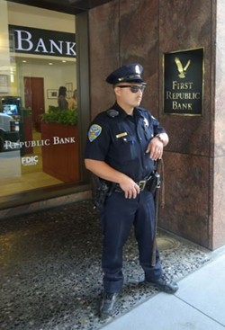 A San Francisco police officer guards the entrance of First Republic Bank's headquarters on Pine Street. - DARWIN BONDGRAHAM