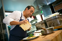 Corporate executive chef Nathan Gabriel grates cheese for a risotto dish. - BERT JOHNSON