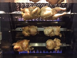 Chickens on the rotisserie at Herb n' Chicken. - YELP USER JOEL D.