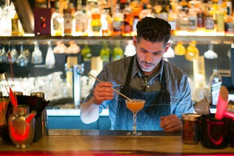 Jason Huffman stirs a cocktail. - BERT JOHNSON