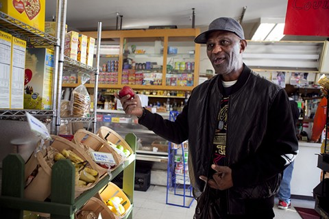 Larry Wilson examines some fruit before choosing what to buy at One-Stop Market in East Oakland, is working with the nonprofit HOPE Collaborative to bring healthy produce into corner stores. - ERIN BALDASSARI