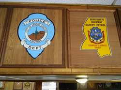 Badges for the Mississippi Highway Patrol and the Apache Junction Police Department hang on the wall inside the Warehouse Bar and Grill. - DARWIN BONDGRAHAM