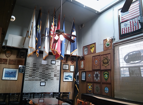 Flags and shields adorn the walls inside the Warehouse Bar and Grill. - DARWIN BONDGRAHAM