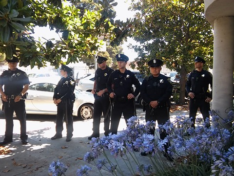Oakland cops wait patiently in the shade during a protest at their union hall today.