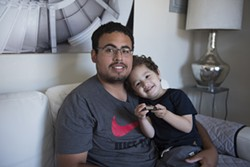 Christian Muñoz and his son in their apartment at 470 Central Avenue in Alameda. - PHOTO BY ROSA FURNEAUX