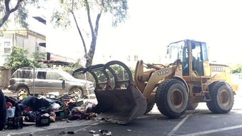"""A """"bulldozer,"""" or wheeled loader, cleaning at a homeless camp on Northgate Avenue in Oakland on May 25. A man says he was hit by what was a smaller, """"Dingo"""" tractor-style vehicle during a clean-up at a different encampment in West Oakland on May 5. - PHOTO BY NICK MILLER"""