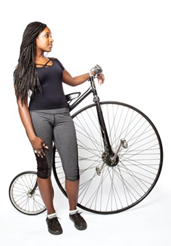 Karima Moore with a unique ride at Laurel Cyclery. - PHOTO BY SAM ZIDE