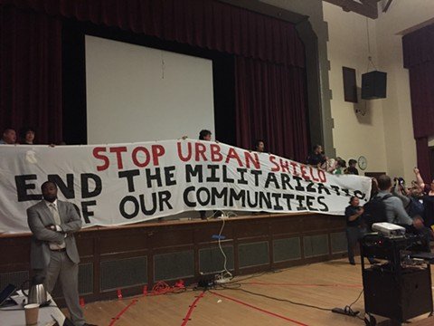 Protesters surround the dais as the council votes to continue with Urban Shield training programs. - PHOTO BY ASHLEY WONG