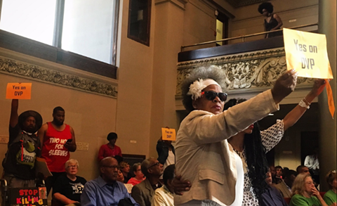 Advocates hold up signs at City Council in support of Department of Violence Prevention - GABRIELLE CANON