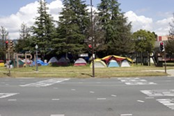 "Several tents dotted the ""Here-There"" homeless encampment on the Berkeley border this past spring. City officials aim to build more transitional housing to move people off of the streets. - HAYDEN BRITTON"