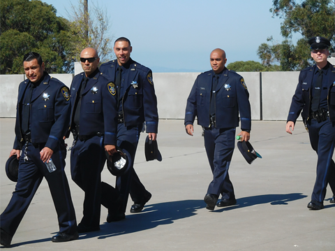 Oakland police officers arriving at today's private ceremony. - DARWIN BONDGRAHAM