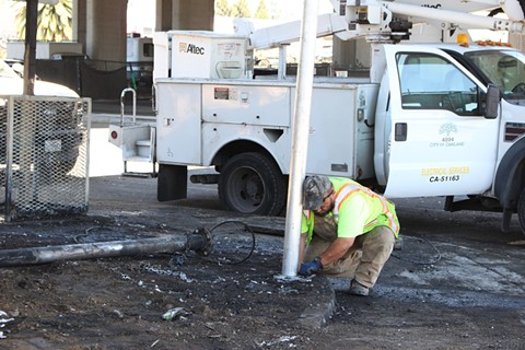 City of Oakland workers replace a stop light this past Monday, which was damaged during a fire at a homeless encampment at Fifth and Market streets. - BRIAN KRANS