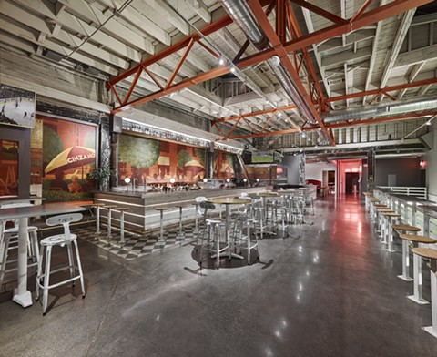 The industrial interior still maintains the original restaurant's murals. - COURTESY OF ADRIAN GREGORUTTI