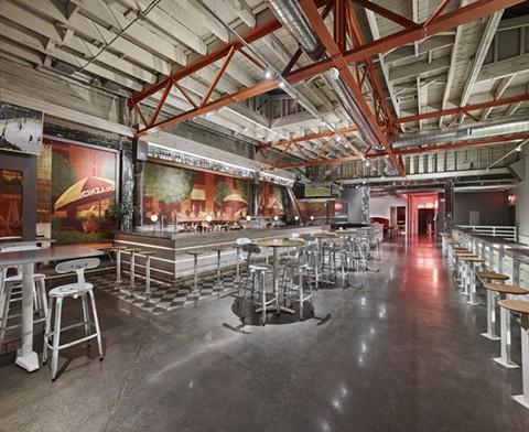 The industrial interior still maintains the original restaurant's murals. - COURTESY OF ADRIAN GREGORUTTI