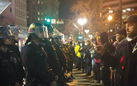 Law-enforcement officers prevent activists from leaving Frank Ogawa Plaza on Friday night.