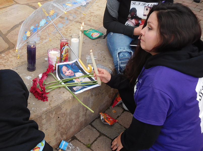 Christina Flores, Elena Mondragon's aunt, lights a candle at yesterday's memorial for the slain teenager.