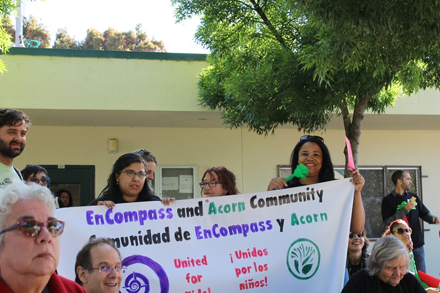 "Teacher Mayra Alvarado (holding left side of sign above ""EmCompass""), told union members during a May 9 rally that she doesn't make enough money to rent or purchase a home in Oakland. - PHOTO BY THERESA HARRINGTON FOR EDSOURCE"