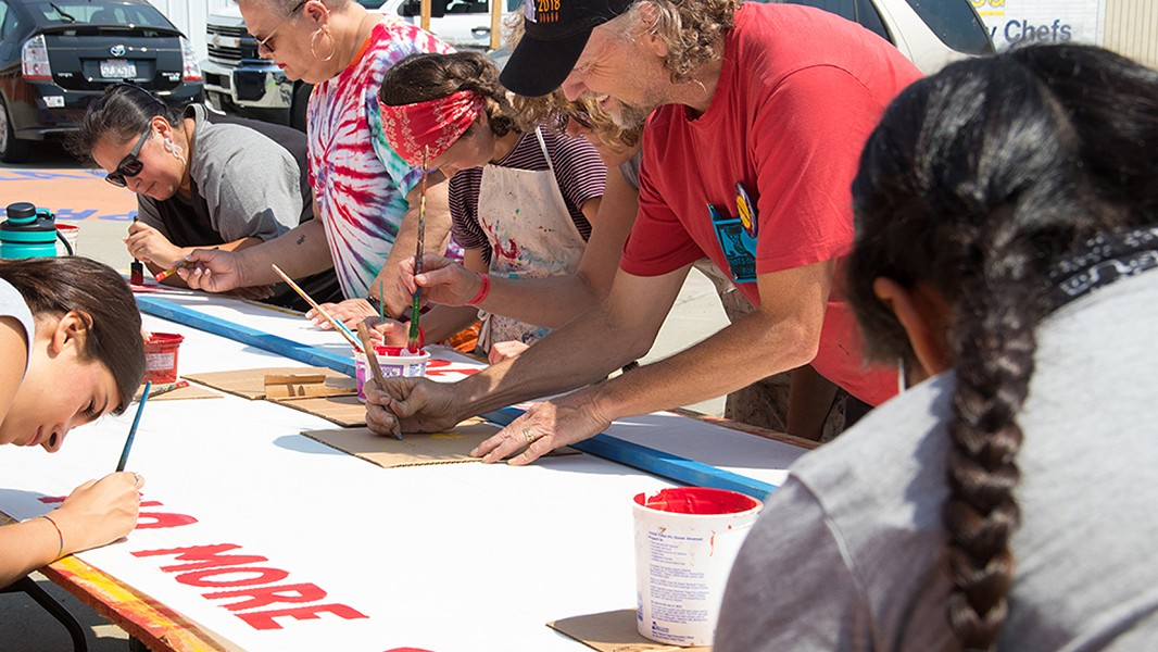 Richmond artist David Solnit worked with volunteers to paint signs ahead of the march. - PHOTO BY PEG HUNTER