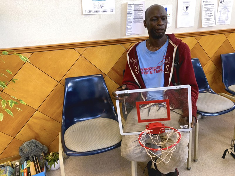 Michael London, 50, sits at the Homeless Action Center in Oakland, waiting to find out if he will be able to return to the Tuff Sheds on Northgate Avenue. He is holding a toy basketball hoop that he has owned since age 13. - PHOTO BY MEG SHUTZER