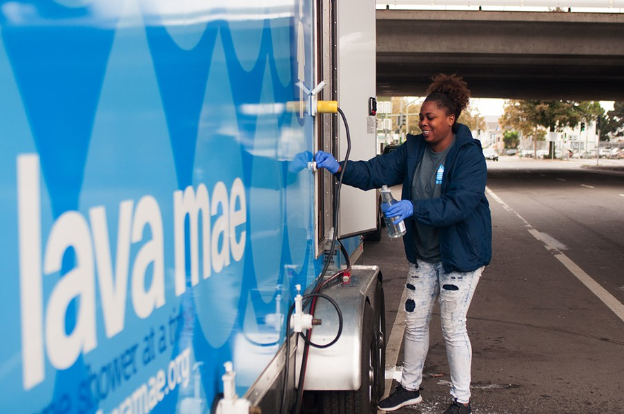 Kaylah Anderson puts water in a bottle of cleaning solution as part of the Lava Mae team setting up for the day at 27th and Northgate. - PHOTO BY DREW COSTLEY