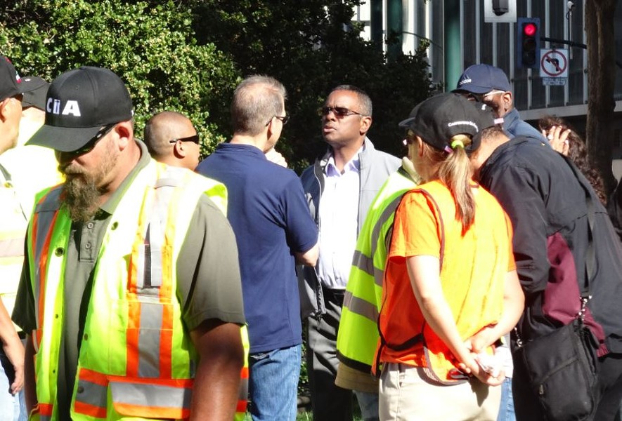 UrbanCore CEO Michael Johnson confers with representatives of the carpenters union outside City Hall on Tuesday. - DARWIN BONDGRAHAM