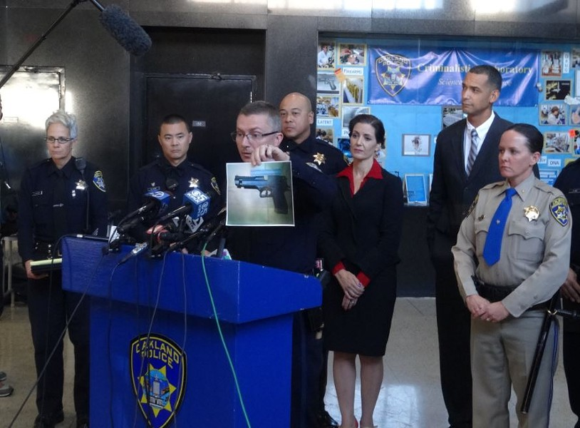 "Oakland police chief Sean Whent displaying a photo of the ""replica"" gun allegedly brandished by a man who was shot and killed on Sunday. - DARWIN BONDGRAHAM"