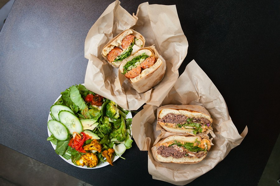 Aunt Malai's Lao sausage sandwich (top), American Kobe roast beef sandwich (right), and the seasonal veggie salad. - BERT JOHNSON