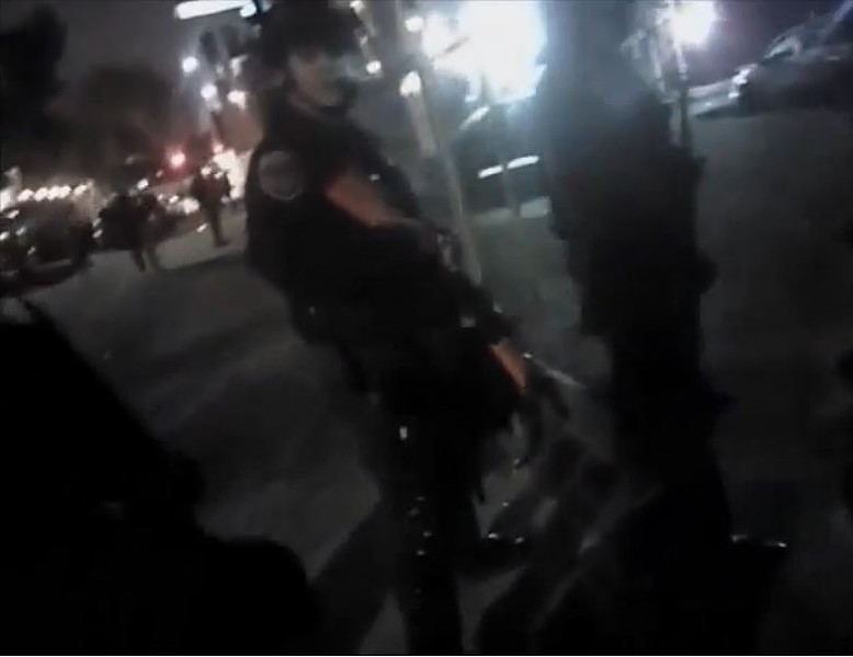 A still image from a police officer body camera video showing a Hayward police officer holding a shotgun loaded with less-lethal ammunition at Berkeley protest in 2014.