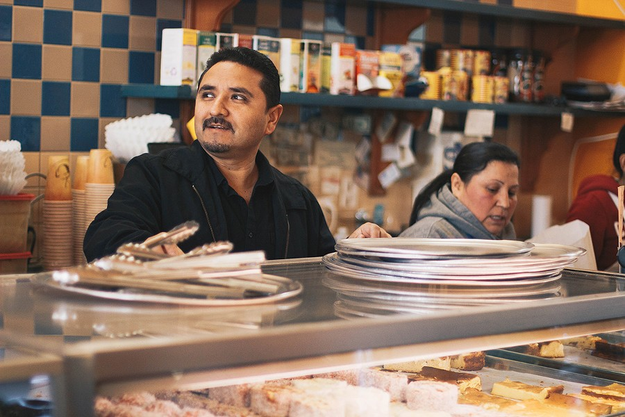 Arturo Peña works the counter on a Sunday morning at his family bakery in the Fruitvale. - HALEIGH HOFF