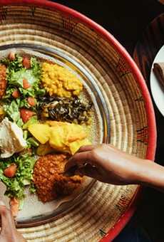 A classic veggie combo — misir wot, gomen, kik alicha, atakilt, and a salad topped with buticha — being shared at Cafe Romanat.