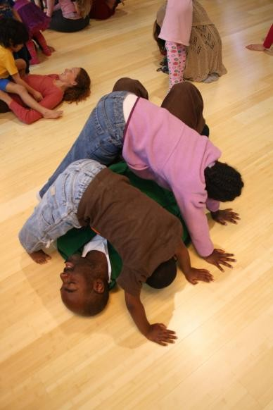 A family performs over and under shapes at a Luna Dance Institute Moving Parents and Children Together class.