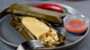 Steamed in banana leaves, the tamales arrive slick and soft.