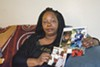 Barbara Doss holding photos of her son, Dujuan Armstrong, who died at Santa Rita Jail.