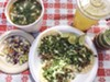 At La Barbacoa, the meat rests on warm tortillas and is topped with onions and cilantro