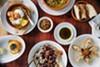 A spread of dishes at Saha, including the lobster knaffe (bottom left), helba & pita (top center), and salmon baklava (bottom right).