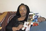 PHOTO BY SCOTT MORRIS - Armstrong's mother, Barbara Doss, holding her son's portrait in her home.