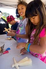 MELISSA BURMAN - Vichara Loch and Nina Corbett make corn-husk dolls at Peralta Hacienda.