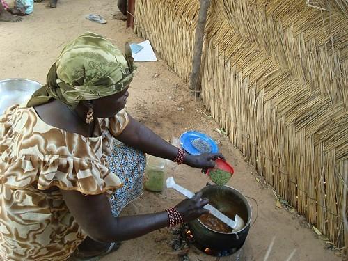 Woman cooking with moringa.
