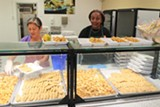 LUKE TSAI - Workers at Oakland High School serve heated-up frozen foods like potatoes and breaded chicken.