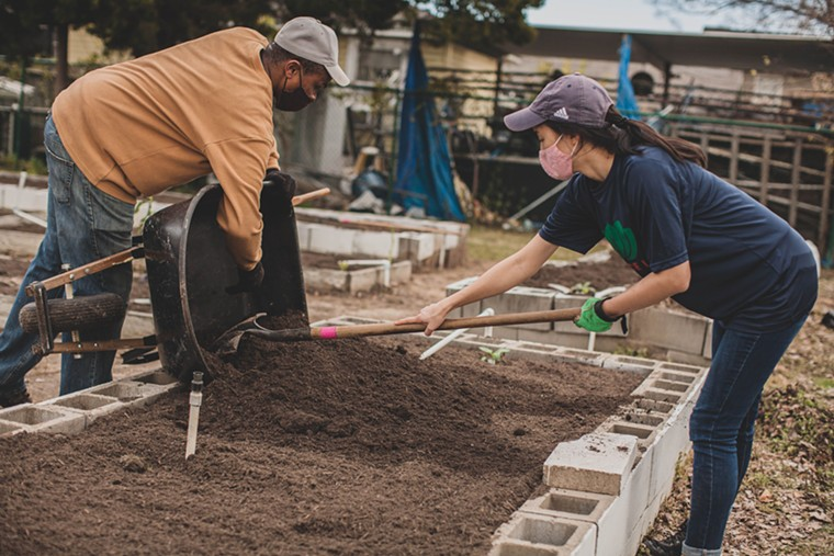 Volunteers help to get Lucille's community garden growing. - PHOTO BY AYAAN AHSAN/AHSAN'S MEDIA HOUSE