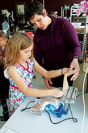 At her birthday party at Copper Pot Cooking Studio, Anna Liberman works with Denise Perry to use a pasta machine to make fettuccine noodles.