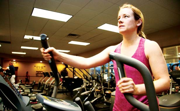 Lindsay Buckles, spinning instructor at Gold's Gym, takes a break from riding in place to walking in place on an elliptical machine. - PHOTO BY PATRICK YEAGLE