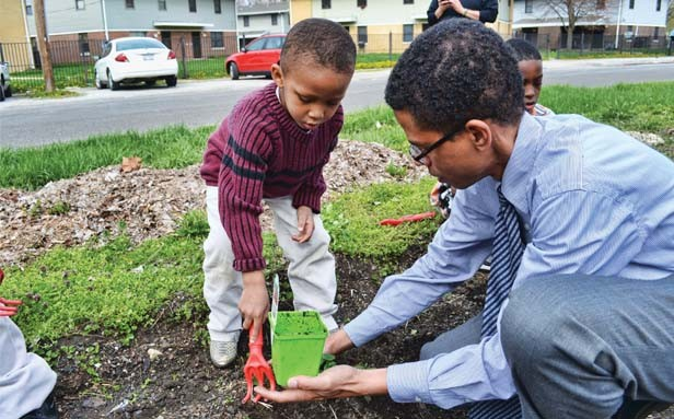 Julius Simmons, executive director of the Springfield Community Federation, helps Kamari Morgan, five, of Springfield, plant strawberries in a community garden near the Springfield Housing Authority. - PHOTO BY JACQUELINE MUHAMMAD