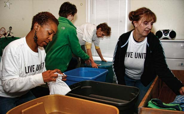 Volunteers Tameka Rushin (left) and Lori Batchelder (right) sort children's clothes at Mini O'Beirne Crisis Nursery, 1011 N. Seventh St.