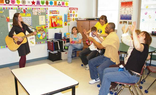 In 2011, students of The Hope Institute for Children and Families enjoy guitar playing and songs with former music therapist Rachel Rambach. - PHOTO BY DAVID HINE